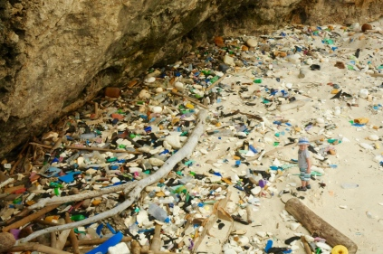 Suchbild mit Kind. Von Indonesien angespülter Müll.